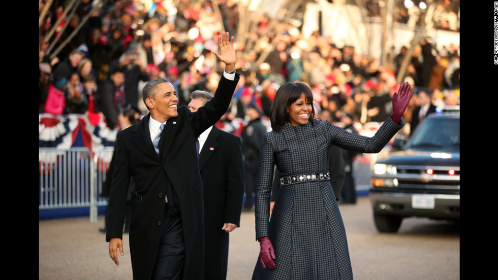 President Barack Obama and first lady Michelle Obama wave to the crowd as they make their way along the parade route on Monday.