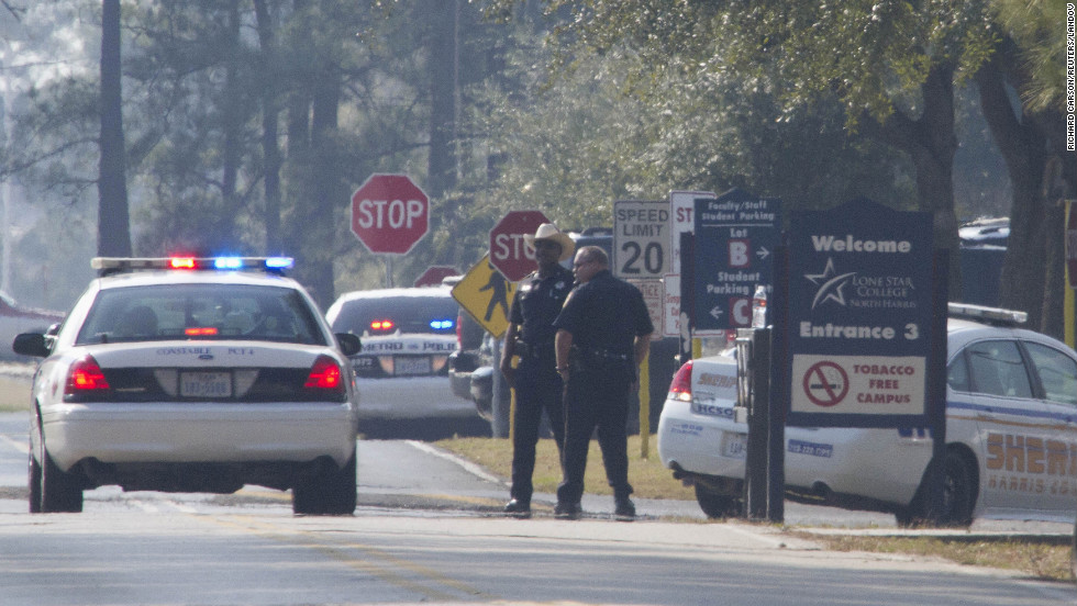 Sheriff's deputies and Houston police stand on the street in front of the campus.