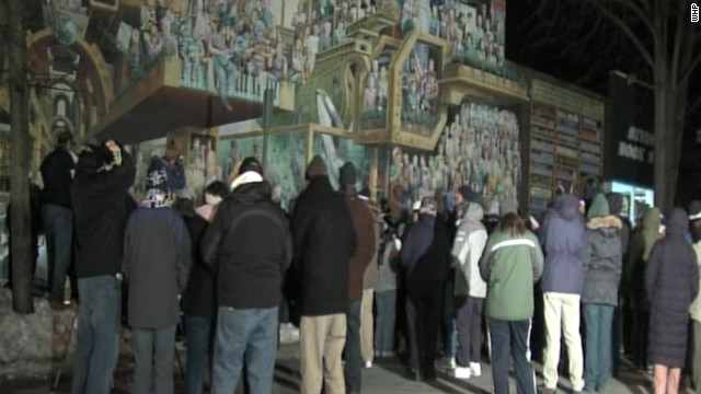 Loyal fans gather Tuesday at a mural depicting late football coach Joe Paterno and other Penn State luminaries.