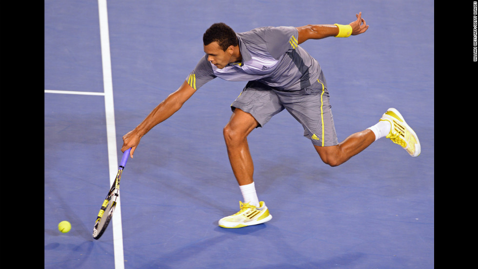 France's Jo-Wilfried Tsonga scoops up a return to Switzerland's Roger Federer during their men's singles match on January 23. Federer defeated Tsonga 7-6 (4), 4-6, 7-6 (4), 3-6, 6-3.