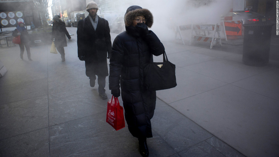 A woman keeps covered up as steam rises from the street on January 23 in New York.