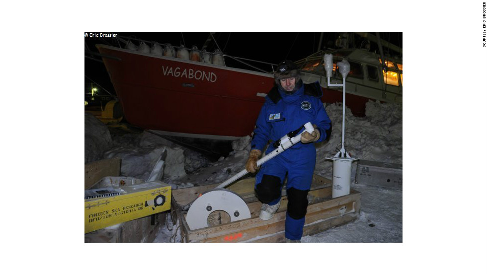 Eric Brossier prepares scientific equipment on the ice just outside Grise Fiord. Brossier's work sees him measure ocean currents, the density of sea ice and weather patterns across large areas of the Canadian Arctic.