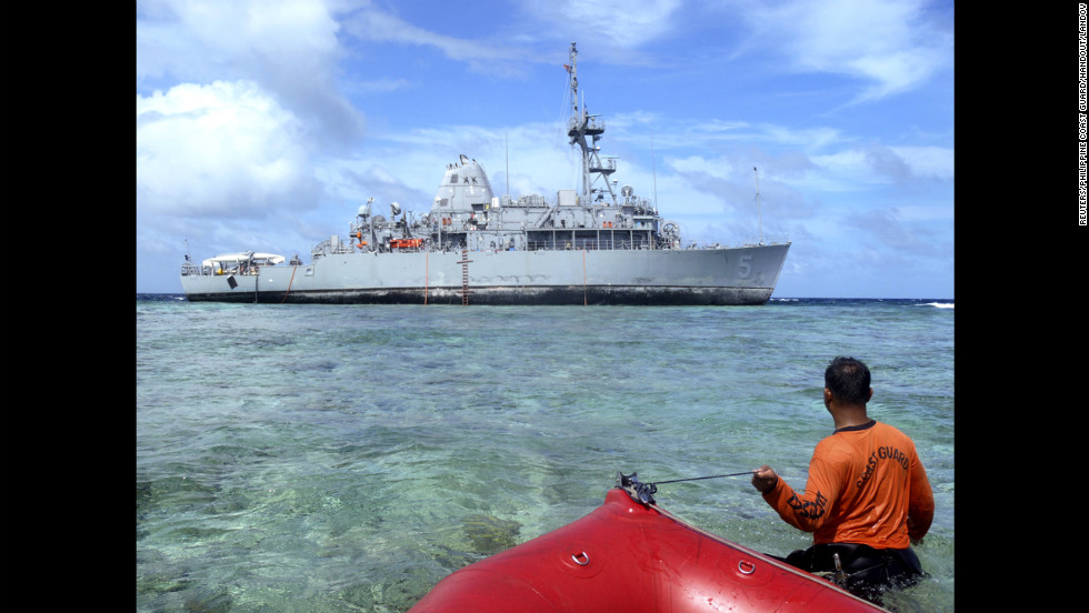 A member of the Philippines coast guard approaches the USS Guardian on Tuesday, January 22, in a handout picture from the Philippines coast guard.