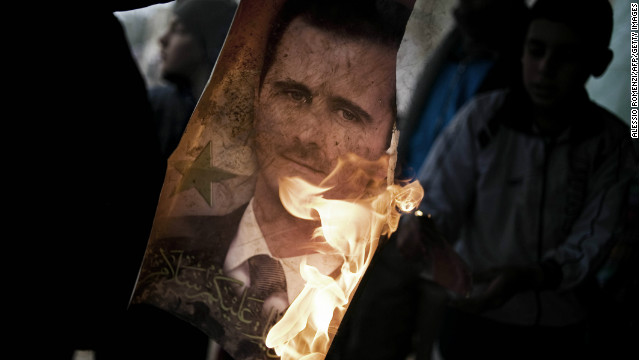 Member of Free Syrian Army holds burning portrait of President Bashar al-Assad in Al-Qsair, January 25, 2012.