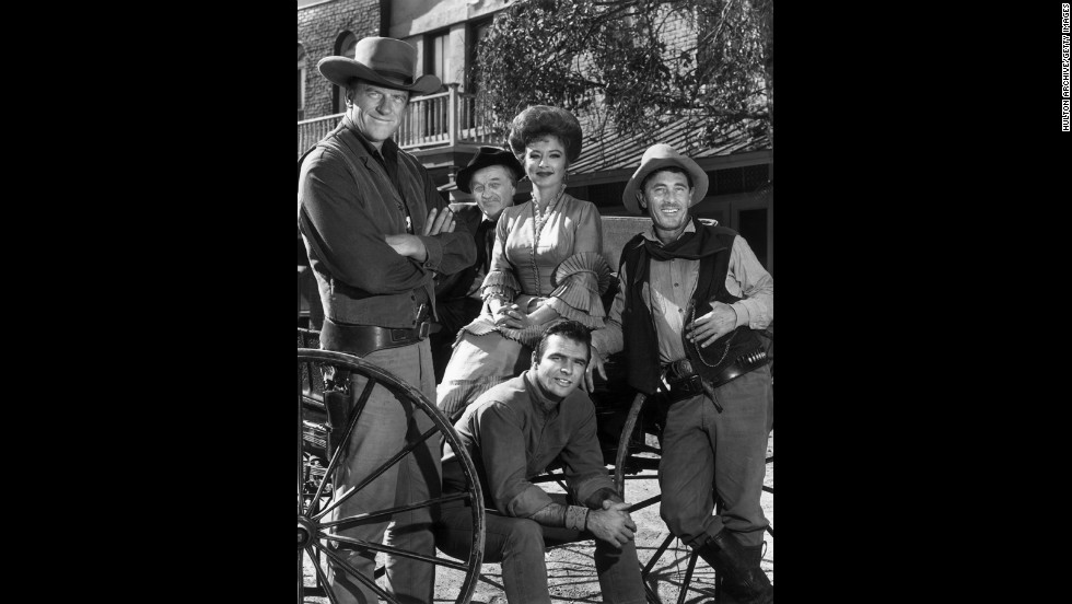 "The cast of ""Gunsmoke"" poses around a wagon in 1962.  From left to right: James Arness, Milburn Stone, Amanda Blake, Ken Curtis and Burt Reynolds (seated)."