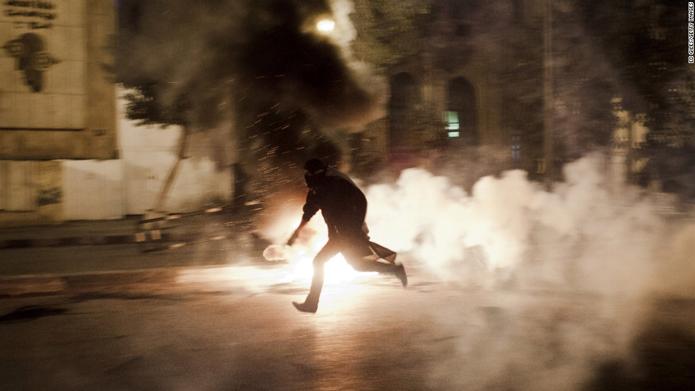 An Egyptian protester runs with a live tear gas canister toward Egyptian riot police on Saturday, January 26, in Cairo.