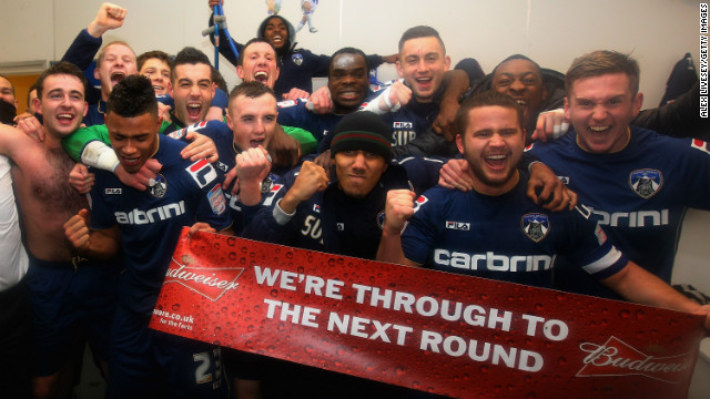 The players of third-tier side Oldham Athletic celebrate a shock FA Cup victory over Premier League Liverpool.