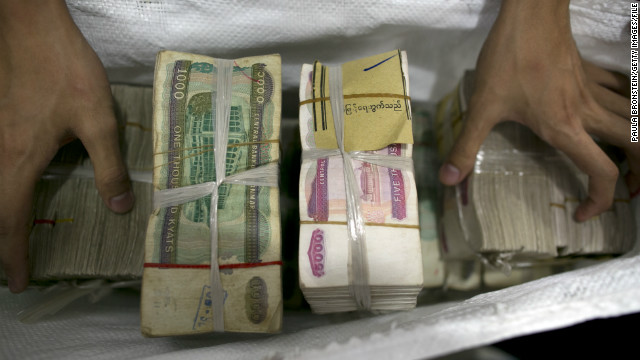 Burmese currency is put into a money bag at a bank in Yangon, Myanmar.