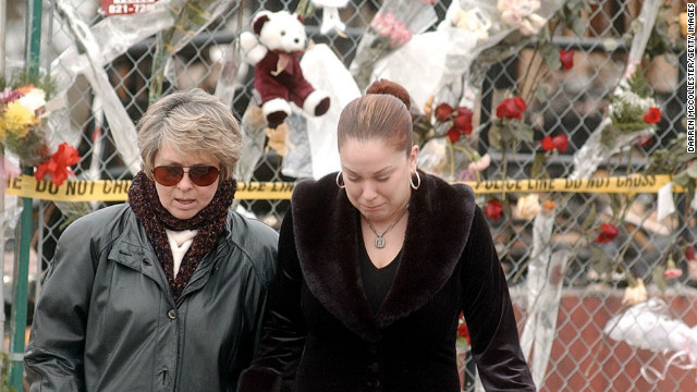 A woman grimaces as she is led away from a makeshift memorial at the site of The Station nightclub fire February 24, 2003 in West Warwick, Rhode Island. The fire took the lives of 97 people when a pyrotechnics display during a rock concert set the club's sound proofing aflame. (Photo by Darren McCollester/Getty Images)