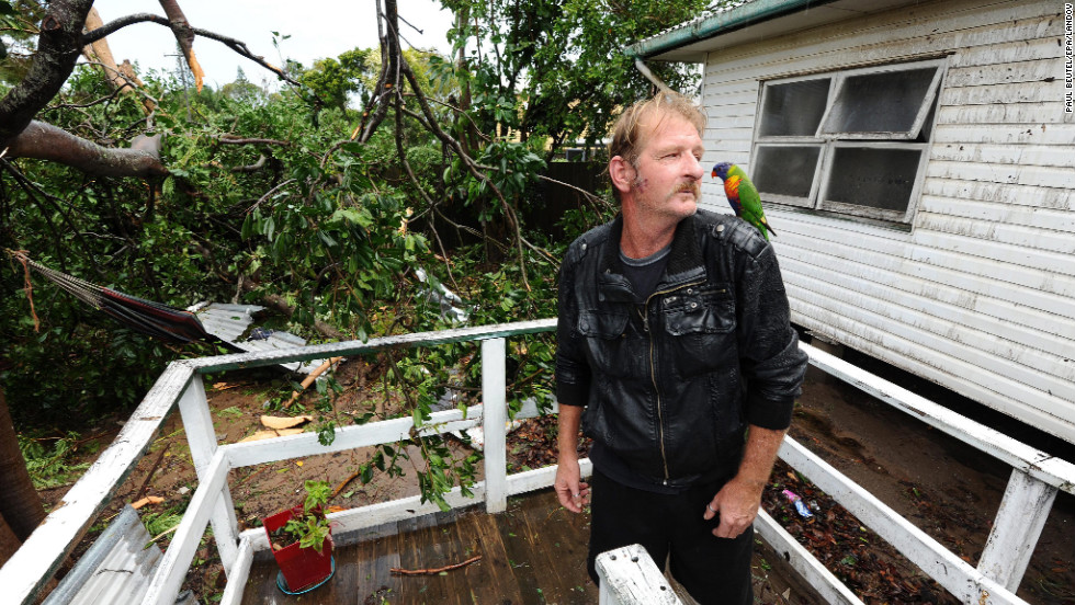 Andrew Cooney and his pet parrot, Jake, survey the uprooted trees outside his storm-damaged home in Bargara, Queensland.