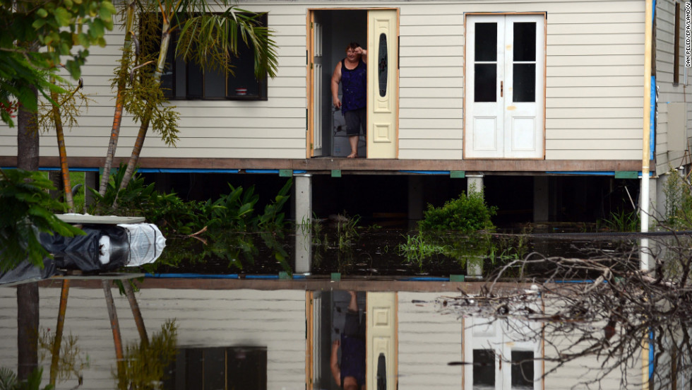 Geraldine Marino stands at her front door surrounded by floodwater on January 28 in Bundaberg.