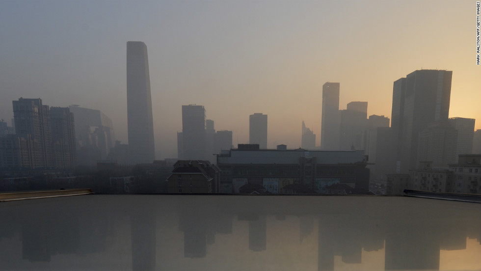 Air pollution hangs over the skyline as the sun rises over the central business district in Beijing on Monday, January 14.