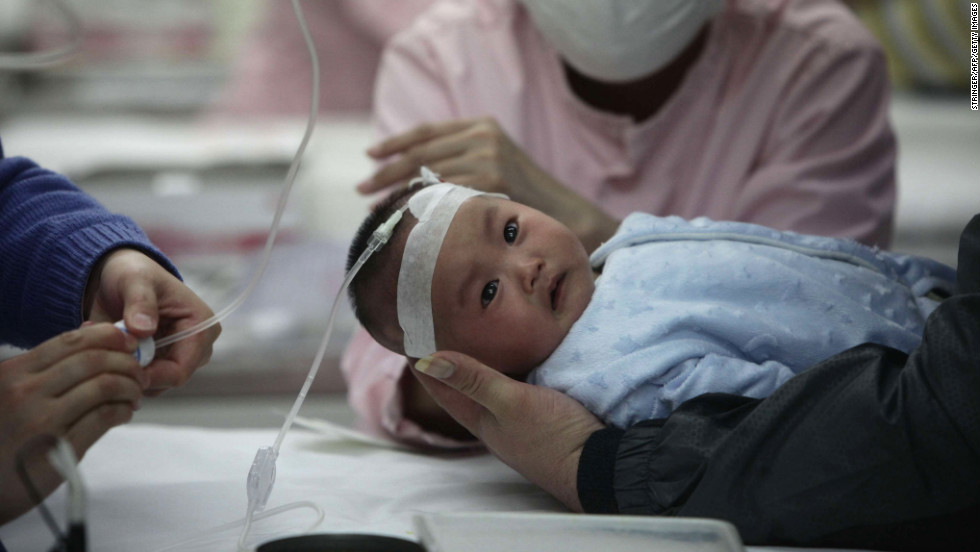 Nurses attend to a baby in the hospital for the flu in Beijing on Sunday, January 13. A Beijing pediatric hospital says it has treated a record 9,000 children this month for respiratory illnesses, most of which doctors and patients blame on the smog, Xinhua reported.