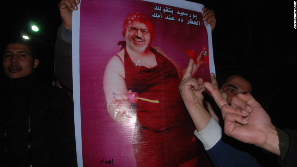 Meanwhile, in Port Said, the announcement sparked violence that led to the deaths of more than 30 people and the imposition of a curfew by President Morsy. A protest was organized to break the curfew. Here a protester carries a picture of Morsy blowing bubbles.