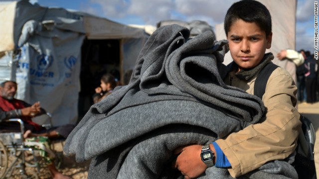 A young boy carries blankets as Syrian refugees go about their daily business in the Za'atari refugee camp on January 29, 2013 in Mafraq, Jordan.