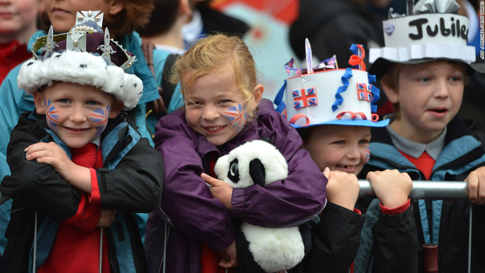 Children wearing homemade paper crowns look on  as Queen Elizabeth II and Prince Philip, Duke of Edinburgh, visit Macartin's Cathedral for Jubilee celebrations in Enniskillen, Northern Ireland.