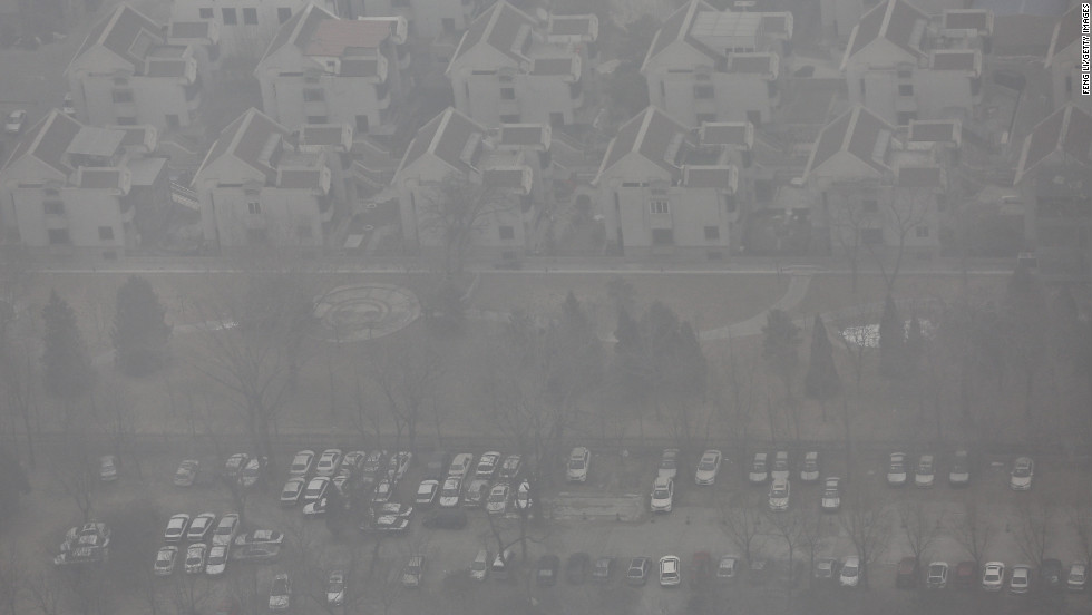 Residential buildings and cars can be made out through the smog in Beijing on January 30.