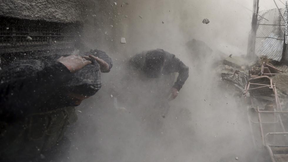 Men shield their heads from debris.