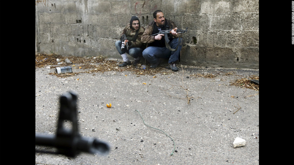 Free Syrian Army fighters take position just before being hit by Syrian Army sniper fire.