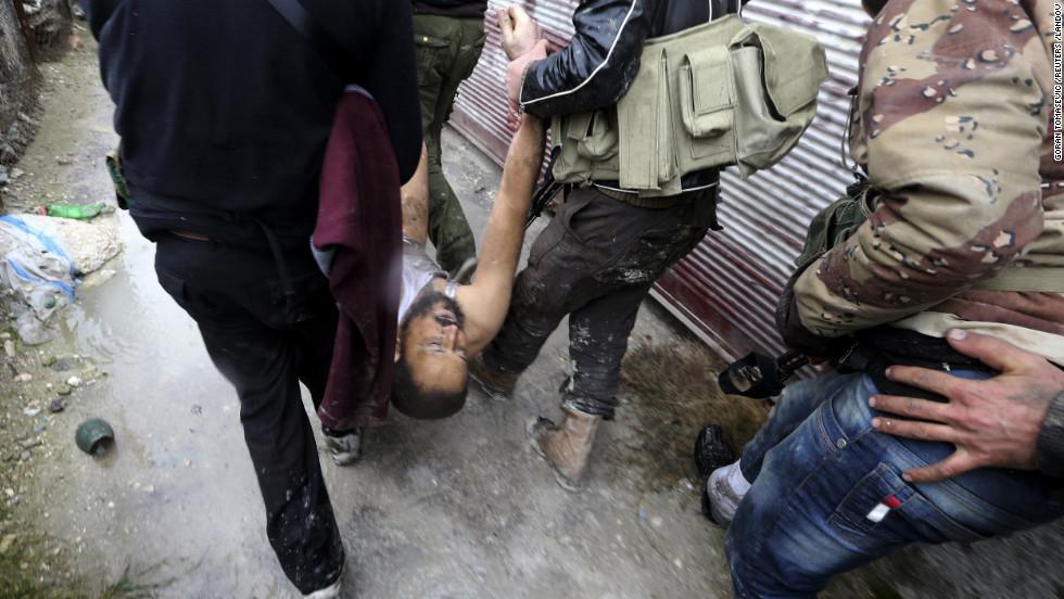 Free Syrian Army men carry their comrade.