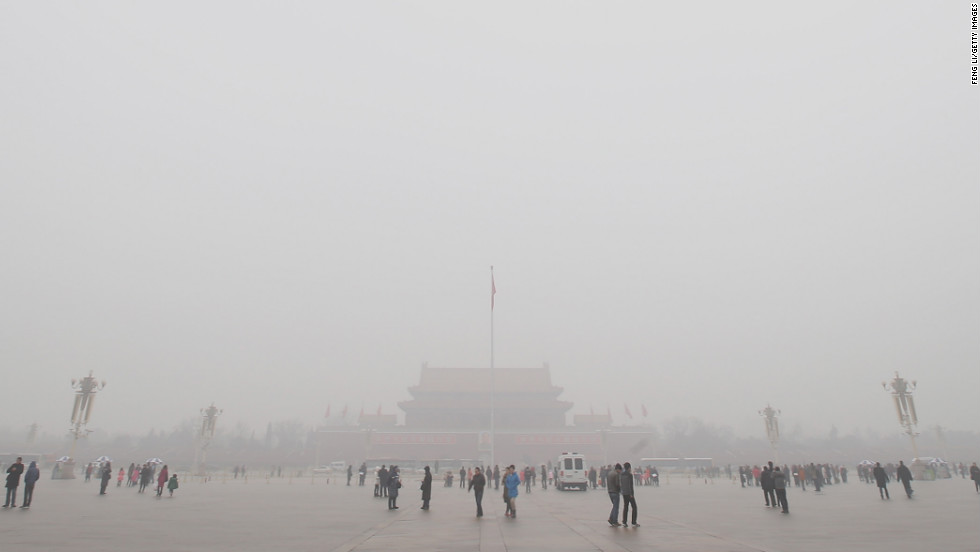 Tourists visit smog-shrouded Tiananmen Square.