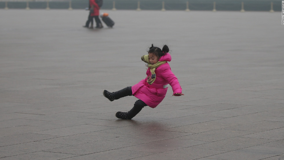 A child slips on frozen pavement in Tiananmen Square.