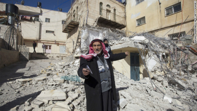 A Palestinian man points toward a home demolished by Israeli bulldozers in Arab East Jerusalem on January 15.