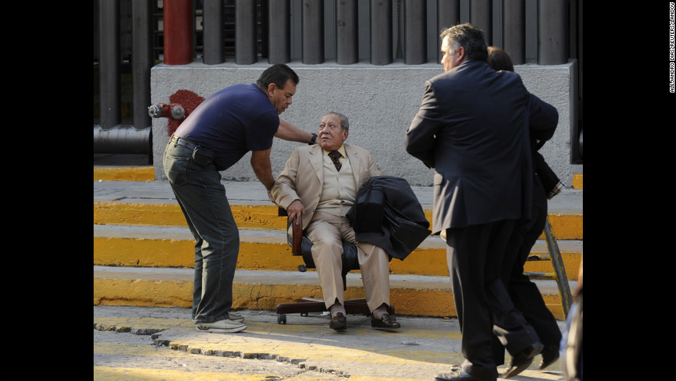 A man at the scene of the blast is helped using a rolling chair near the scene of the explosion.