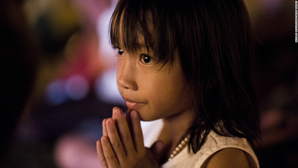 A Cambodian girl prays for the late former King Norodom Sihanouk in front of the Royal Palace on Thursday.