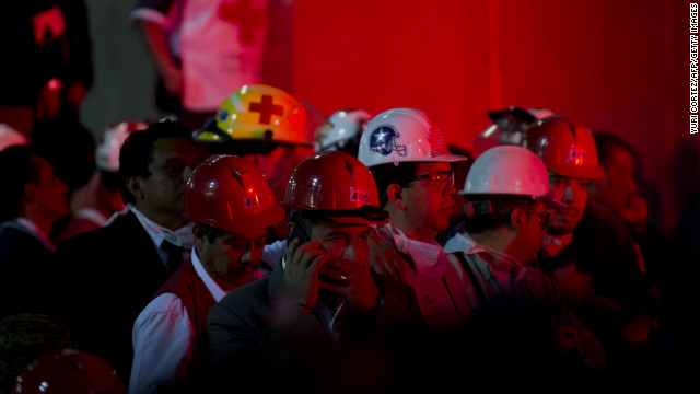 Employees and rescue workers listen as the Minister of the Interior, Miguel Angel Osorio Chong (out of frame) addresses a press conference at the headquarters of state-owned Mexican oil giant Pemex in Mexico City on January 31, 2013, following a blast inside the building.