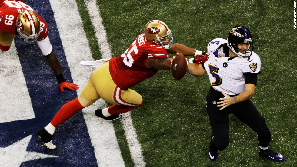 Quarterback Joe Flacco of the Ravens attempts to escape pressure from Ahmad Brooks of the 49ers.