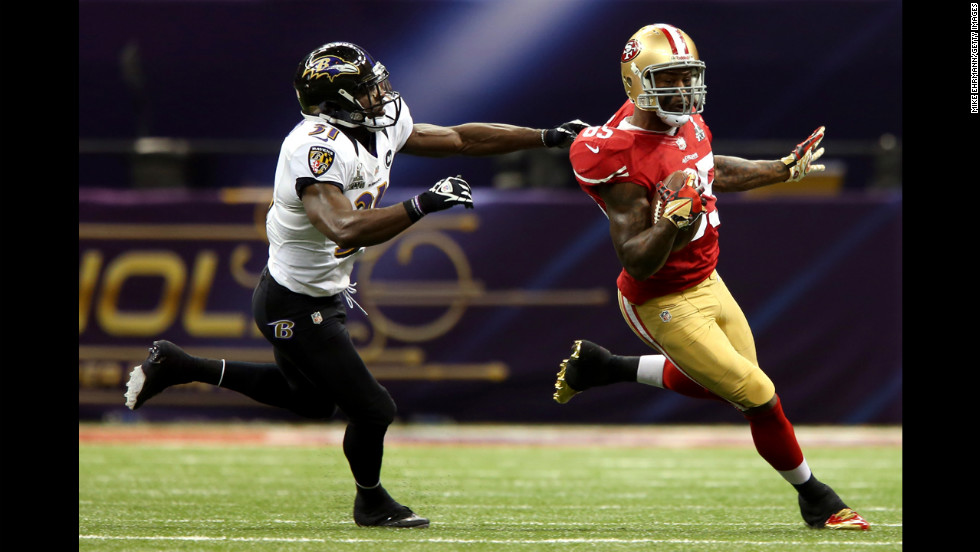 Bernard Pollard of the Baltimore Ravens tries to tackle Vernon Davis of the San Francisco 49ers.