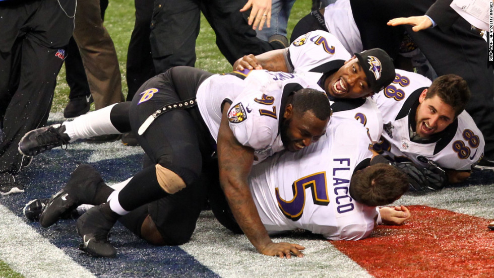 Quarterback Joe Flacco is tackled by teammates while celebrating after the game.
