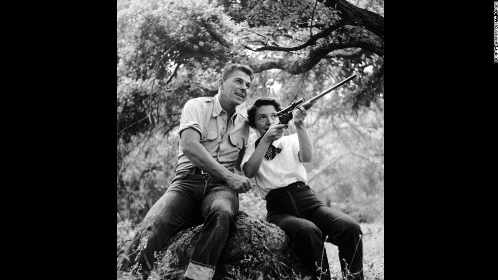 Ronald Reagan watches as his wife, Nancy, aims a rifle at their ranch in Malibu, California, in 1954.