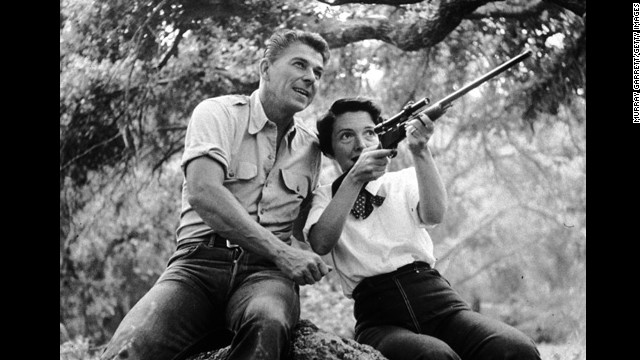 1954:  EXCLUSIVE American actor Ronald Reagan watches as his wife, Nancy, aims a rifle while they sit on a large rock outdoors at their ranch in Malibu, California. Both wear jeans and their shirt sleeves rolled up.  (Photo by Murray Garrett/Getty Images)