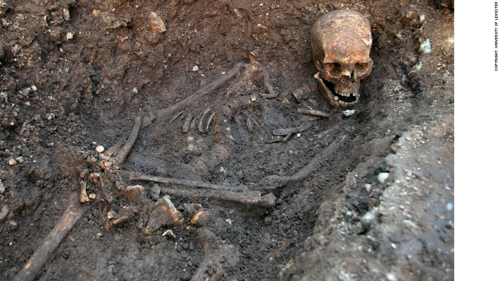 The skeleton being excavated, showing the curve in the spine and the way the head had been squashed into the grave. The hands may have been tied.