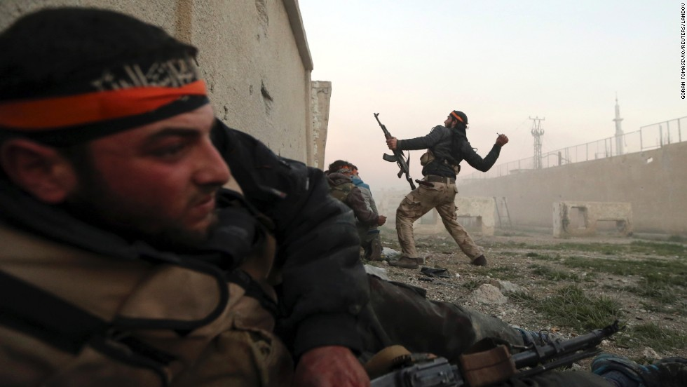 A rebel fighter throws a hand grenade inside a Syrian Army base in Damascus on February 3.