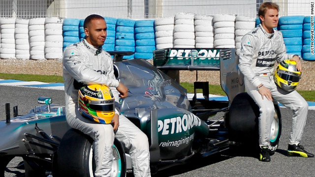 Lewis Hamilton and Nico Rosberg pose with the new Mercedes car for the 2013 Formula One season.
