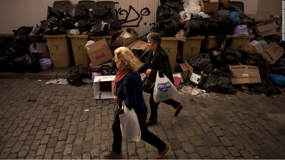 Two women walk past trash piles on February 4.