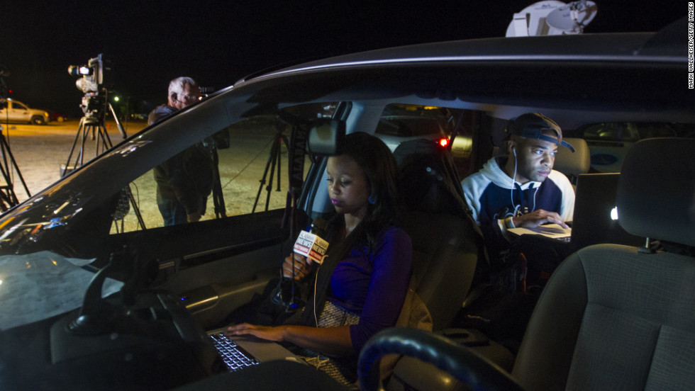Reporter Ashley Thompson, left, and Marcus Effinger work on a report for Alabama News Network from their vehicle at the site of the standoff on February 4.