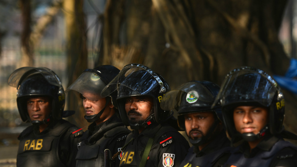 Rapid Action Battalion personnel keep watch outside the International Crimes Tribunal court in Dhaka on February 5.