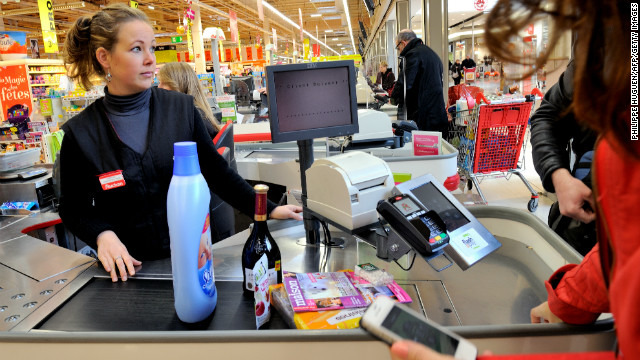 A customer pays at a register with a smartphone application in December at a Auchan supermarket in northern France.