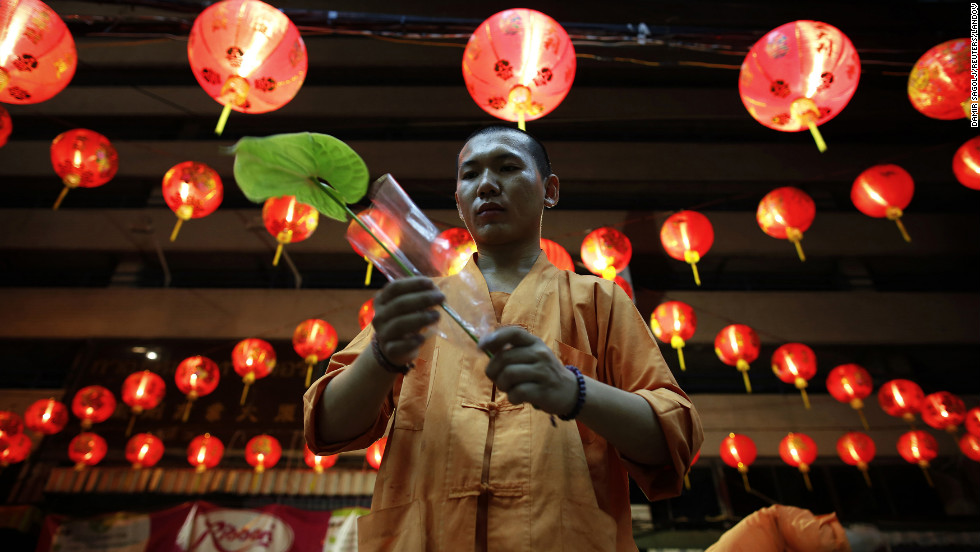 A man helps decorate a temple ahead of Chinese New Year festivities Friday, February 8, in Bangkok, Thailand. <br />