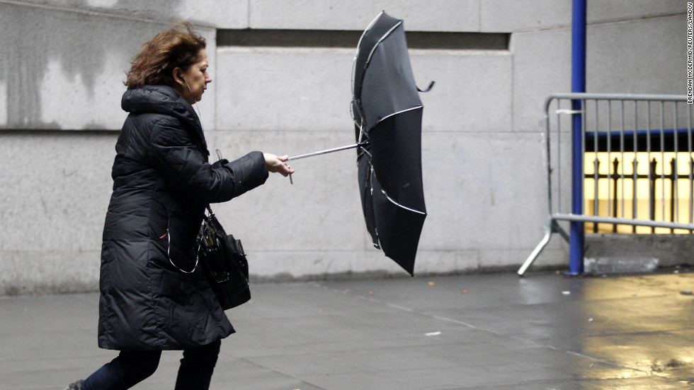 A woman struggles with her umbrella in New York's Financial District on February 8. Accumulations of up to a foot of snow are expected in the Big Apple.