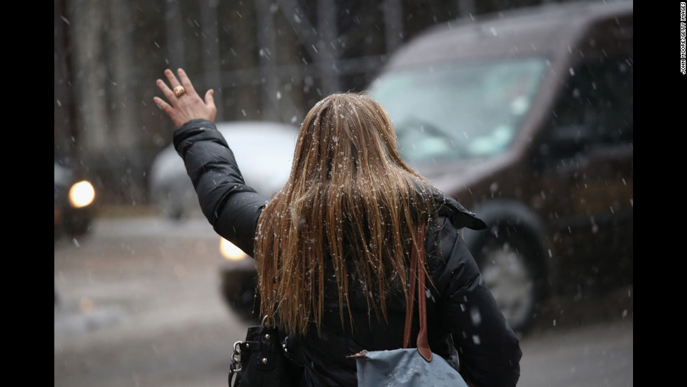 A woman hails a taxi as snow and freezing rain fall over Midtown Manhattan as the city braced for the major storm on Friday.