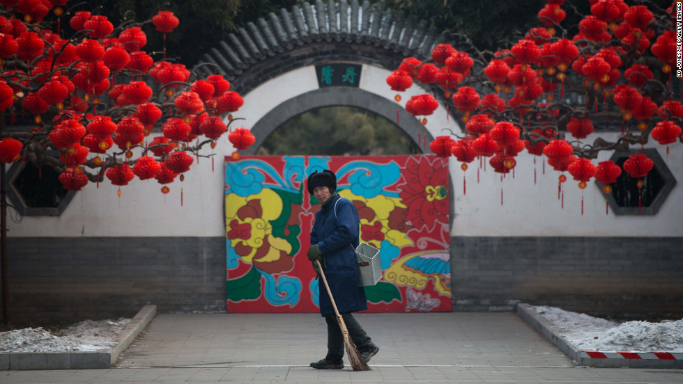 A worker walks past red lanterns hanging from a tree in Ditan Park in Beijing on February 9, a day before the Chinese New Year.