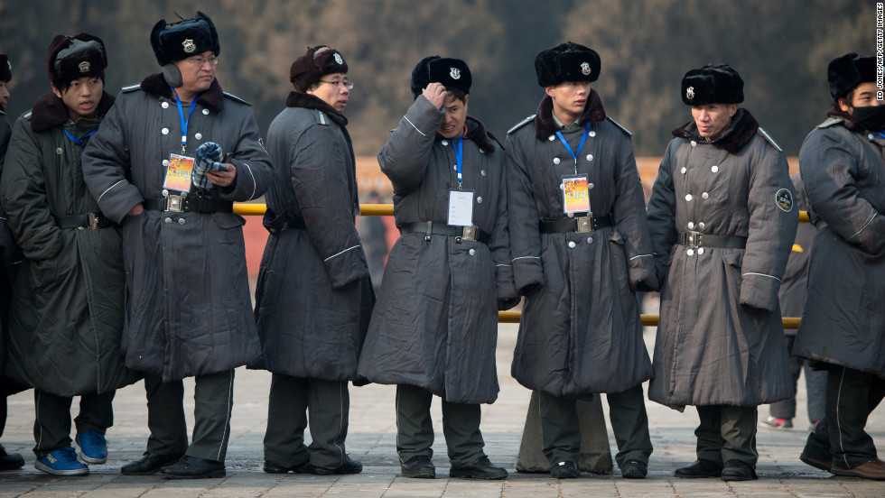Security guards watch as performers take part in a traditional Qing Dynasty ceremony in Beijing on February 9.