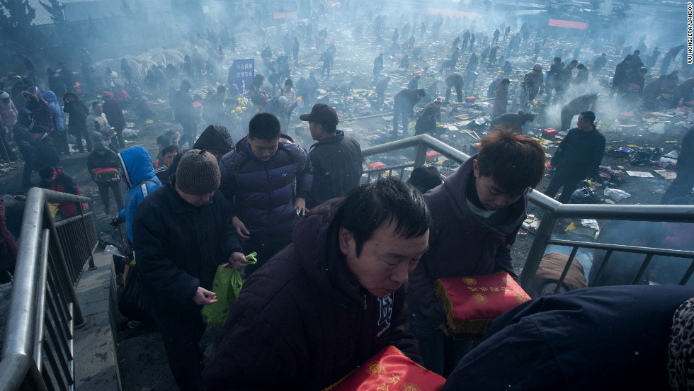 "Two Chinese men carry small caskets to be burned at a cemetery in Qingdao, China on Saturday, February 9. Chinese people offer sacrifices to their departed family members one day before the <a href=""http://travel.cnn.com/7-ways-celebrate-chinese-new-year-395376"">Chinese New Year</a>."