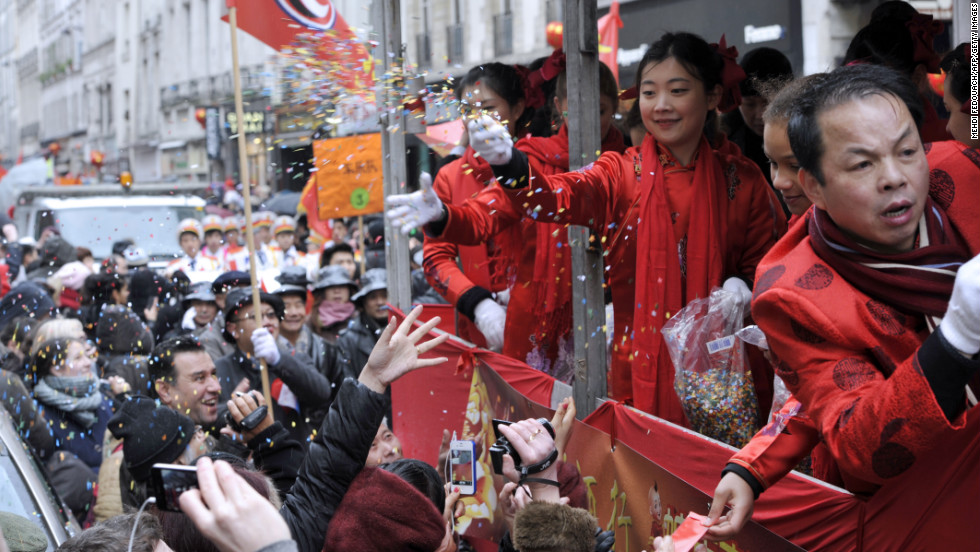 Performers throw confetti into the crowd during a parade in Paris on February 10.