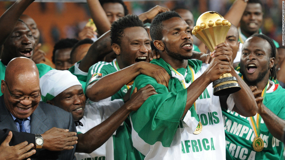 Nigeria's captain Joseph Yobo holds the Africa Cup of Nations trophy, which had been handed to him by South African President Jacob Zuma (L) at Soccer City stadium in Johannesburg.